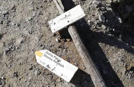 Zniszczona tabliczka na przełęczy Krzyżne
